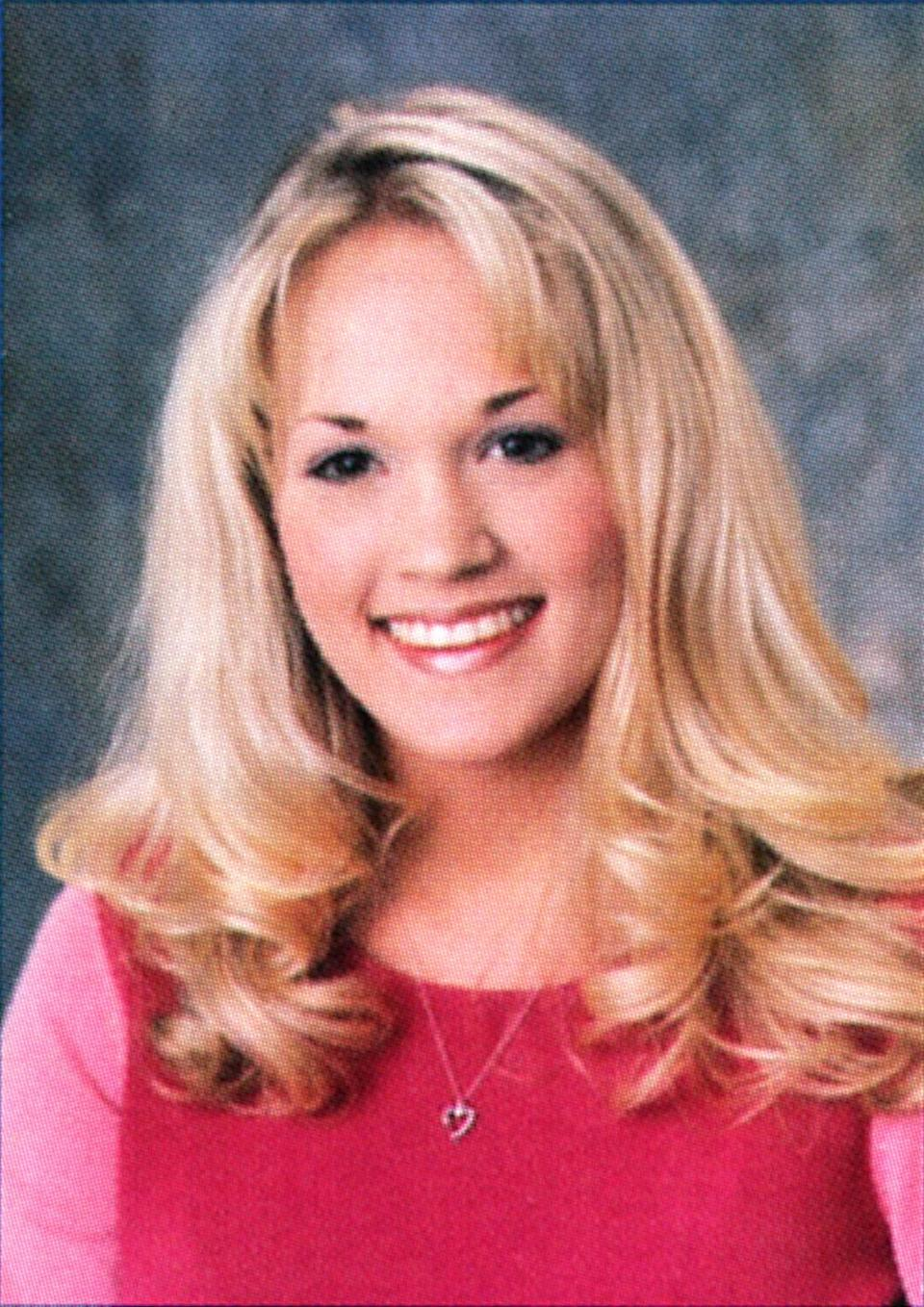 <p>Country's sweetheart, Carrie Underwood, lives up to her nickname with blonde ringlets, glossy pink lips, and a matching pink top in her Oklahoma high school senior portrait. <i>(Photo: Seth Poppel/Yearbook Library)</i> </p>