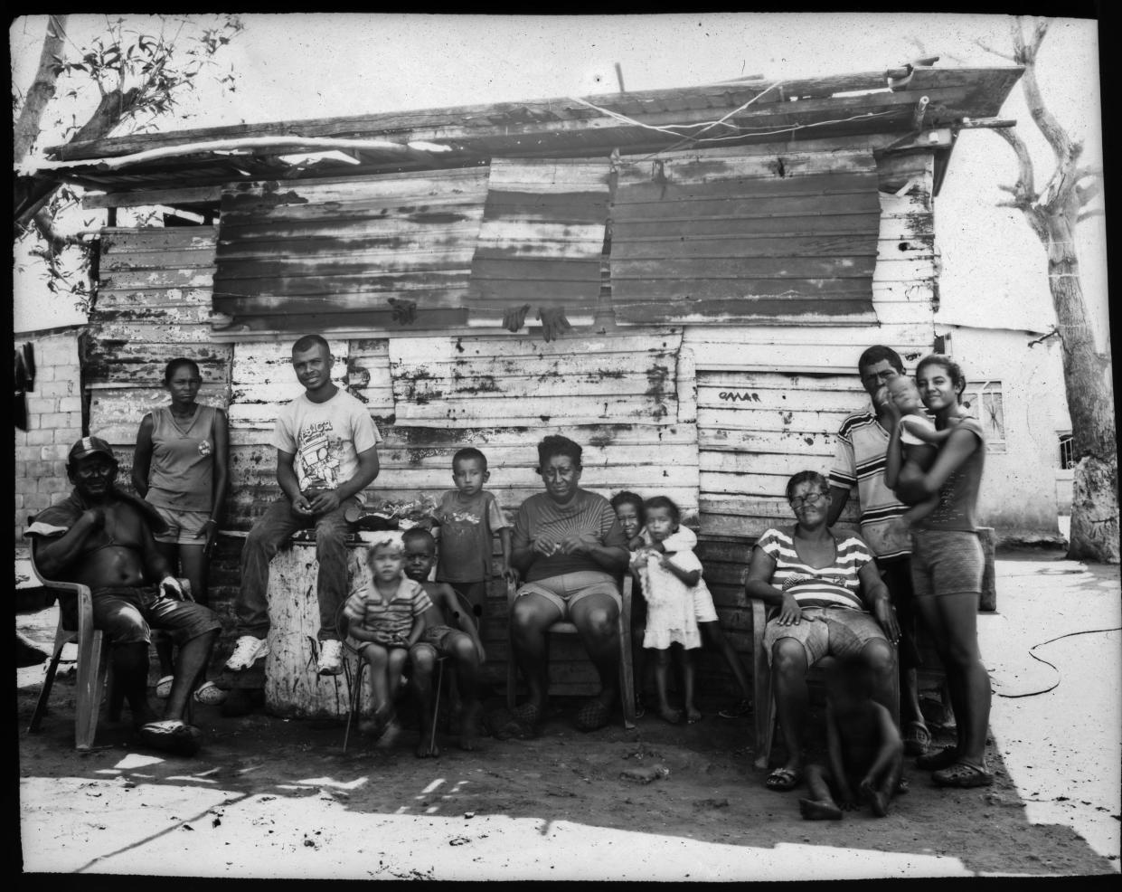 The Elizalzabal and Silva families, who fish for a living, pose for a portrait outside one of their family's homes, on the shore of oil-contaminated Lake Maracaibo in Cabimas, Venezuela. (Photo: Rodrigo Abd/AP)