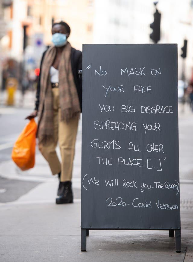 A person wearing a face mask walks past a sign encouraging the use of face coverings outside a cafe in central London