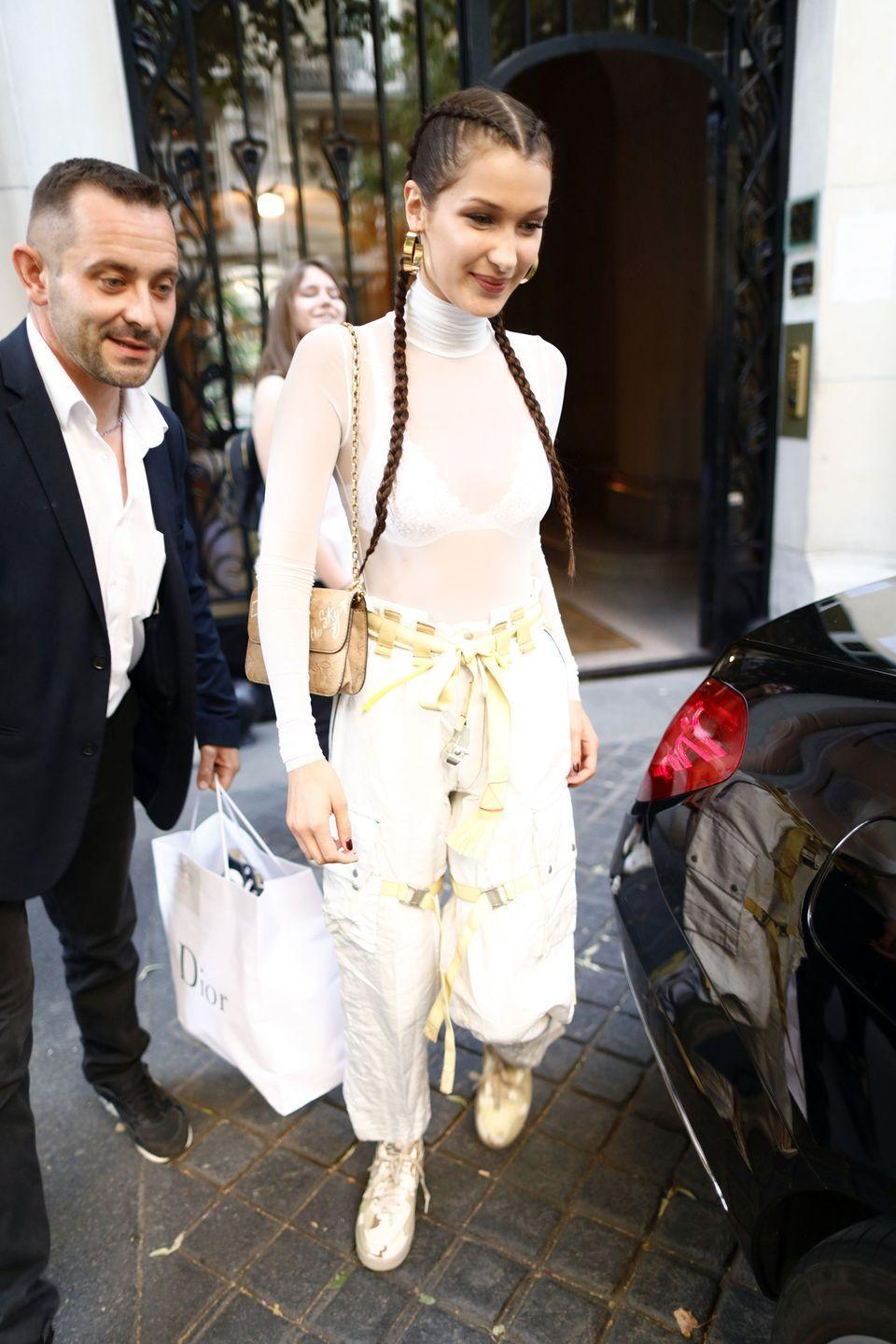 <p>In Sakuanz Fall 2017 white pants, a white mesh turtleneck, Dior purse and Nike army-patterned kicks while out in Paris. </p>