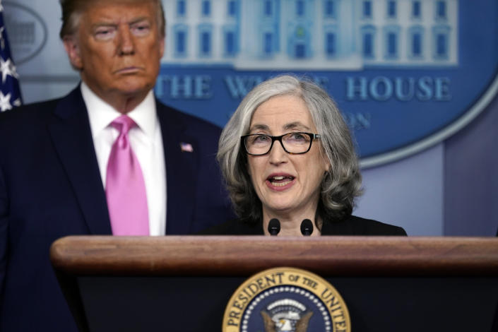 Dr. Anne Schuchat speaks at a podium with then-President Donald Trump behind her