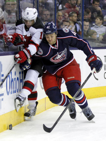 Columbus Blue Jackets' Dalton Prout, right, checks New Jersey Devils' Stephen Gionta in the first period of an NHL hockey game in Columbus, Ohio, Tuesday, Oct. 22, 2013. (AP Photo/Paul Vernon)
