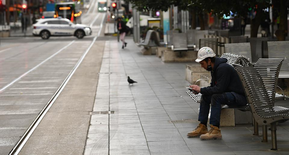 A construction worker is seen sitting on a bench along Bourke Street in Melbourne, Friday, July 23, 2021.