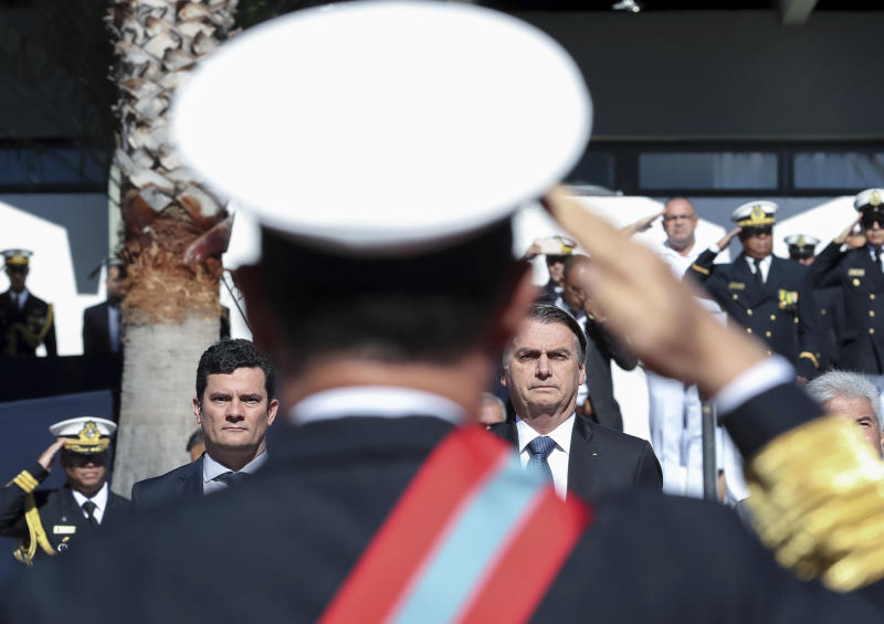 In this photo released by Brazil's Presidential Press Office, Brazil's President Jair Bolsonaro, right, and Justice Minister Sergio Moro attend a military ceremony in Brasilia, Brazil, Tuesday, June 11, 2019.  Moro has met with President Jair Bolsonaro, two days after press reports accused him of allegedly coordinating with prosecutors when he was a judge. (Marcos Correa/Brazil's Presidential Press Office via PA)