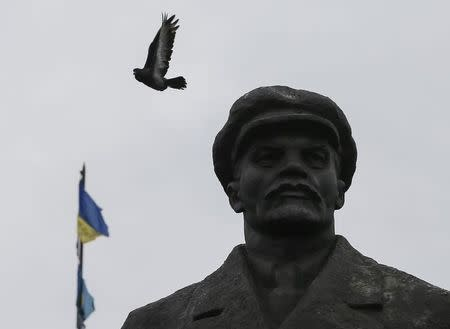 A pigeon flies from a monument of Soviet leader Vladimir Lenin in front of the mayor's office, with Ukrainian flags in central Slaviansk