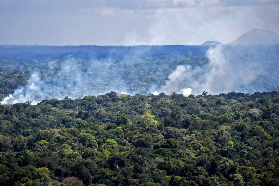 Aerial view showing smoke from a fire billowing from the Amazon rainforest in Oiapoque, Amapa state, Brazil, on the border with French Guiana, on October 31, 2020, where members of the Brazilian Armed Forces are conducting a military exercise as part of the Agata operation. - The Agata operation carried out by the Armed Forces, Federal Police, Federal Revenue and the Brazilian Institute for the Environment and Renewable Natural Resources (IBAMA), consists in combating drug and arms trafficking, smuggling, illegal mining and fishing, boat theft and irregular transportation of wood and fuel, in the states of Para and Amapa. (Photo by NELSON ALMEIDA / AFP) (Photo by NELSON ALMEIDA/AFP via Getty Images)