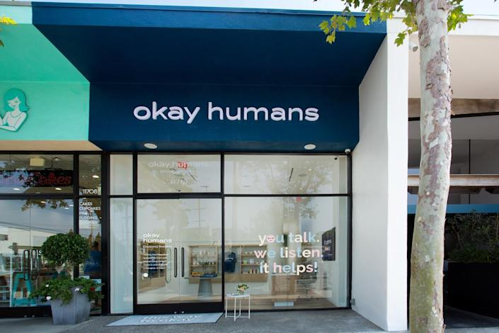 """The exterior of a storefront with an """"Okay Humans"""" sign at the top. On the window, it says, """"you talk, we listen. it helps!"""""""
