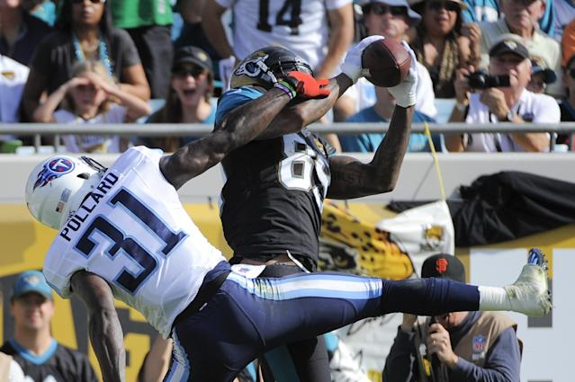 Jacksonville Jaguars tight end Marcedes Lewis (89) catches a 4-yard pass in the end zone for a touchdown in front of Tennessee Titans strong safety Bernard Pollard (31) in the first half of an NFL football game in Jacksonville, Fla., Sunday, Dec. 22, 2013.(AP Photo/Stephen Morton)