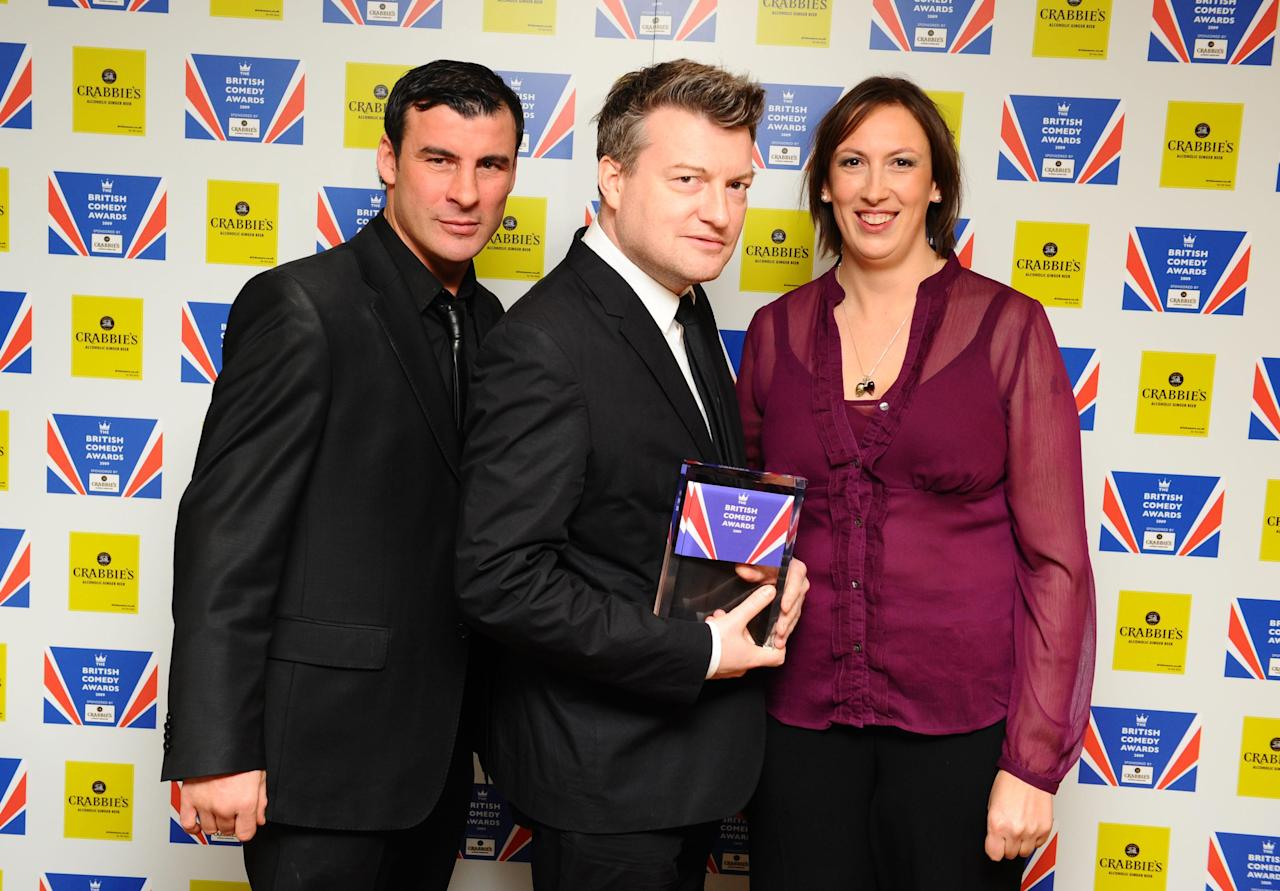 Charlie Brooker (centre) wins Best Male Comedy Newcomer for You Have Been Watching, presented by Joe Calzaghe and Miranda Hart, at the British Comedy Awards 2009 at London Television Studios.   (Photo by Ian West/PA Images via Getty Images)