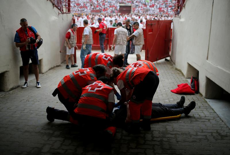 An injured reveller is helped by medical staff during the first running of the bulls at the San Fermin festival in Pamplona, Spain, July 7, 2019. (Photo: Jon Nazca/Reuters)