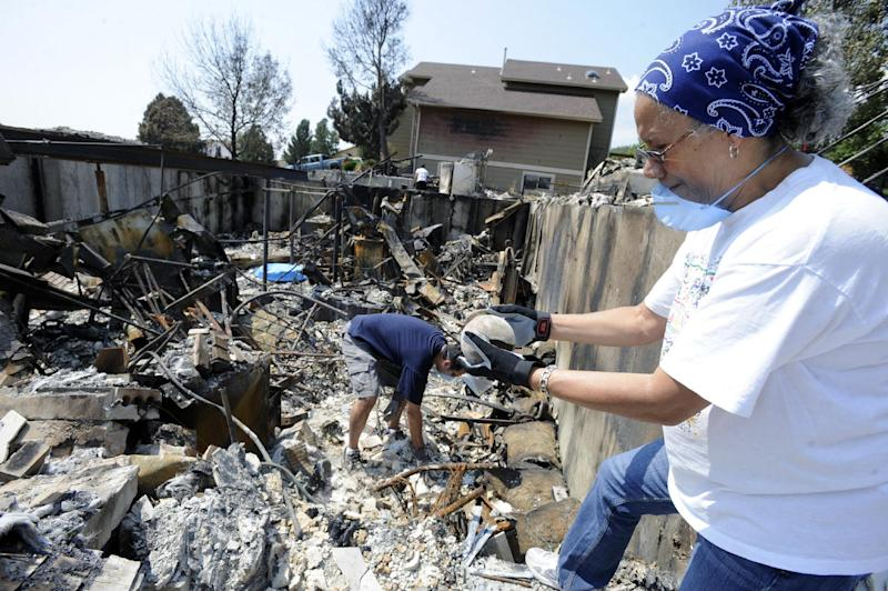 Iris Johnson and her son Adrian Johnson dig through to salvage items from the remains of their home in the Mountain Shadows neighborhood of Colorado Springs, Colo., Thursday, July 5, 2012. Their home was destroyed in the Waldo Canyon fire, which has burned about 28 square miles and has damaged or destroyed almost 350 homes since it started June 23. (AP Photo/The Colorado Springs Gazette, Jerilee Bennett)