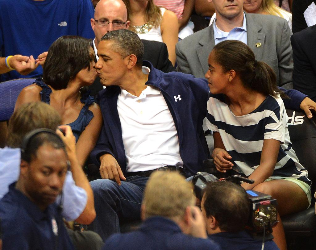 It took a little prodding, but President Barack Obama and First Lady Michelle Obama finally gave in and smooched for the kiss cam during the U.S. men's Olympic basketball team's exhibition game against Brazil at Washington DC's Verizon Center on Monday night. At first the couple refused to kiss when the camera zeroed in on them, which drew boos from the crowd, but after they got a second chance, the Obamas puckered up as daughter Malia (and the rest of the world!) looked on. (7/16/2012)
