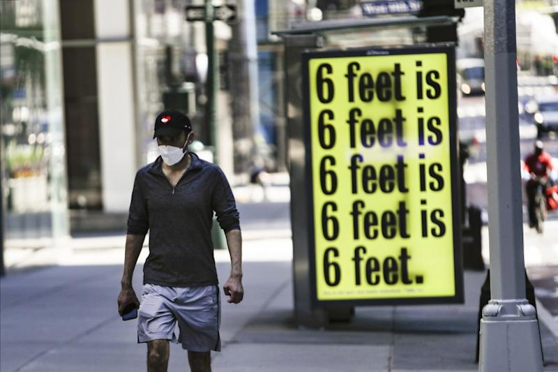 A pedestrian walks past a social-distancing reminder in New York.