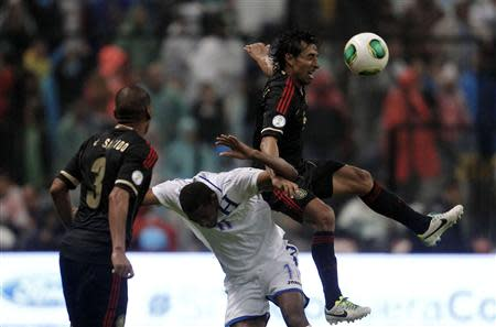 Mexico's Fernando Arce (R) jumps for the ball against Honduras' Jerry Bengtson as Mexico's Carlos Salcido looks on during their 2014 World Cup qualifying soccer match at Azteca stadium in Mexico City September 6, 2013. REUTERS/Edgard Garrido