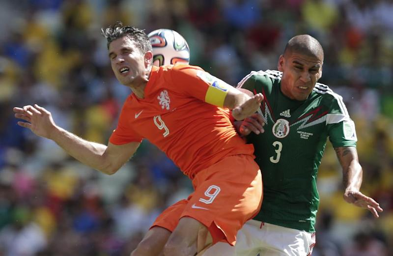 Netherlands' Robin van Persie, left, and Mexico's Carlos Salcido challenge for the ball during the World Cup round of 16 soccer match between the Netherlands and Mexico at the Arena Castelao in Fortaleza, Brazil, Sunday, June 29, 2014