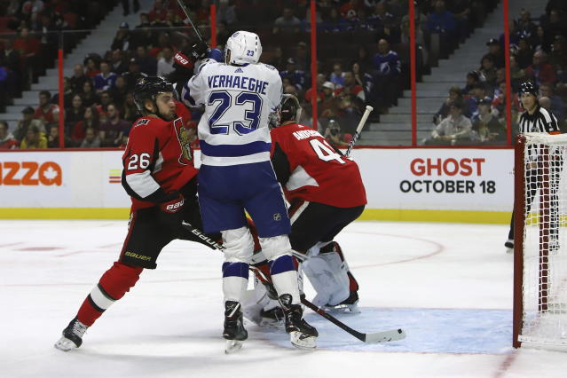 Ottawa Senators defenceman Erik Brannstrom (26) checks Tampa Bay Lightning centre Carter Verhaeghe (23) in front of Senators goaltender Craig Anderson (41) during first period of NHL hockey action in Ottawa, Saturday, Oct. 12, 2019. (Fred Chartrand/The Canadian Press via AP)
