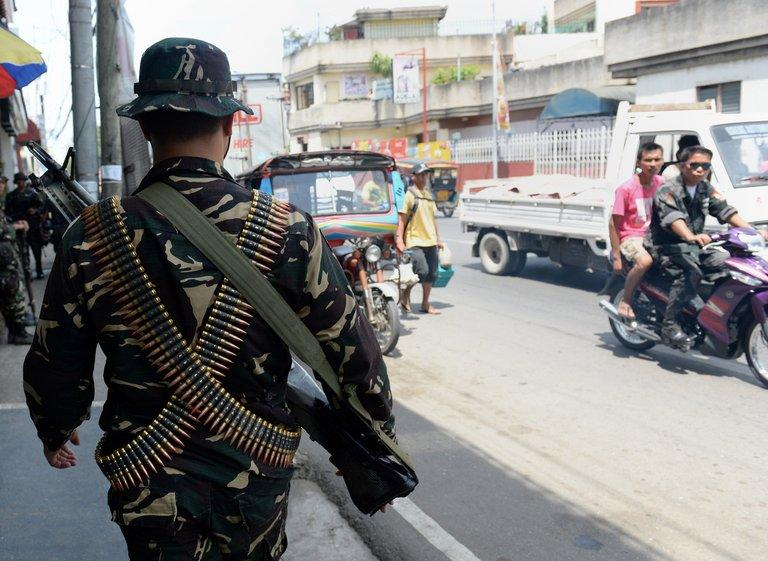 Philippine soldiers patrol as government forces clash with Muslim rebels in Zamboanga City, on September 21, 2013