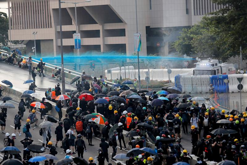 Anti-government protesters are sprayed with a water cannon during a demonstration near Central Government Complex in Hong Kong, Sunday, Sept. 15, 2019. Police fired a water cannon and tear gas at protesters who lobbed Molotov cocktails outside the Hong Kong government office complex Sunday, as violence flared anew after thousands of pro-democracy supporters marched through downtown in defiance of a police ban. (AP Photo/Kin Cheung)