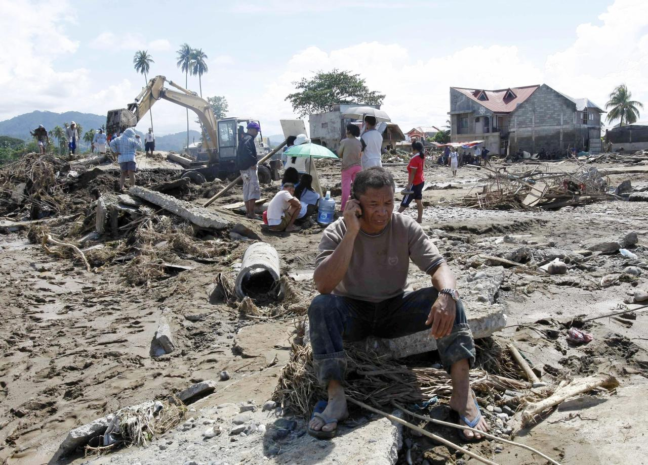 Cristio Tingson, foreground, talks on his cell phone as workers use a backhoe to search for victims of his buried house Sunday, Dec. 18, 2011 at Iligan city in southern Philippines. Tropical storm Washi blew away Sunday after devastating the southern Philippines with flash floods that killed hundreds of people as they slept and turned two coastal cities into a muddy wasteland filled with overturned cars and uprooted trees. Rescuers dug up eleven bodies but not Tingson's wife and three children. (AP Photo/Bullit Marquez)
