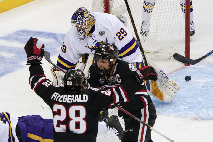 St. Cloud State's Spencer Meier (9) celebrates with Kevin Fitzgerald (28) after he scored on Minnesota State goaltender Dryden McKay (29) during the first period of an NCAA men's Frozen Four hockey semifinal in Pittsburgh, Thursday, April 8, 2021. (AP Photo/Keith Srakocic)
