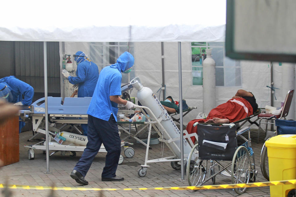 A medical worker wheels an oxygen tank to be used to treat patients at an emergency tent erected to accommodate a surge in COVID-19 cases, at Dr. Sardjito Central Hospital in Yogyakarta, Indonesia, Sunday, July 4, 2021. A number of COVID-19 patients died amid an oxygen shortage at the hospital on the main island of Java following a nationwide surge of coronavirus infections. (AP Photo/Kalandra)