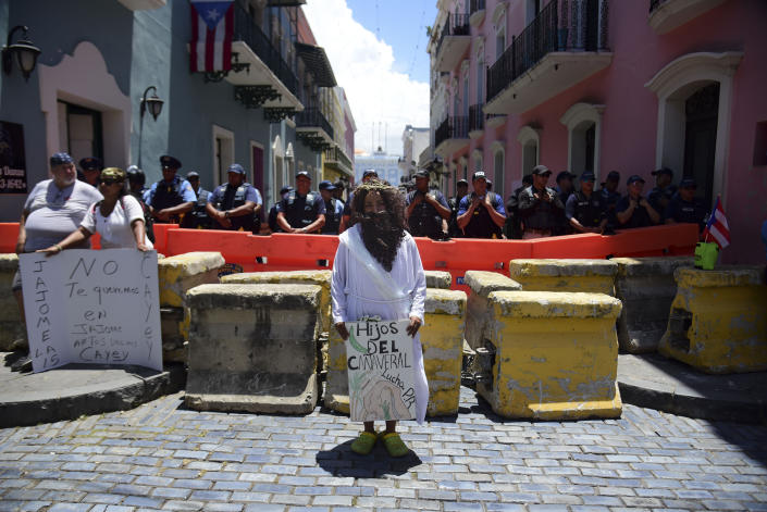 """A demonstrator dressed as Jesus holds a Spanish message: """"Children of the cane field fight for Puerto Rico,"""" in front of a police perimeter around the La Fortaleza residence of Gov. Ricardo Rosselló in San Juan, Puerto Rico, Wednesday, July 17, 2019. (Photo: Carlos Giusti/AP)"""