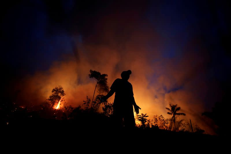 FILE PHOTO: A fire burns as back burning is used to create a firebreak to stop the progress of a fire at a tract of the Amazon jungle in Apui