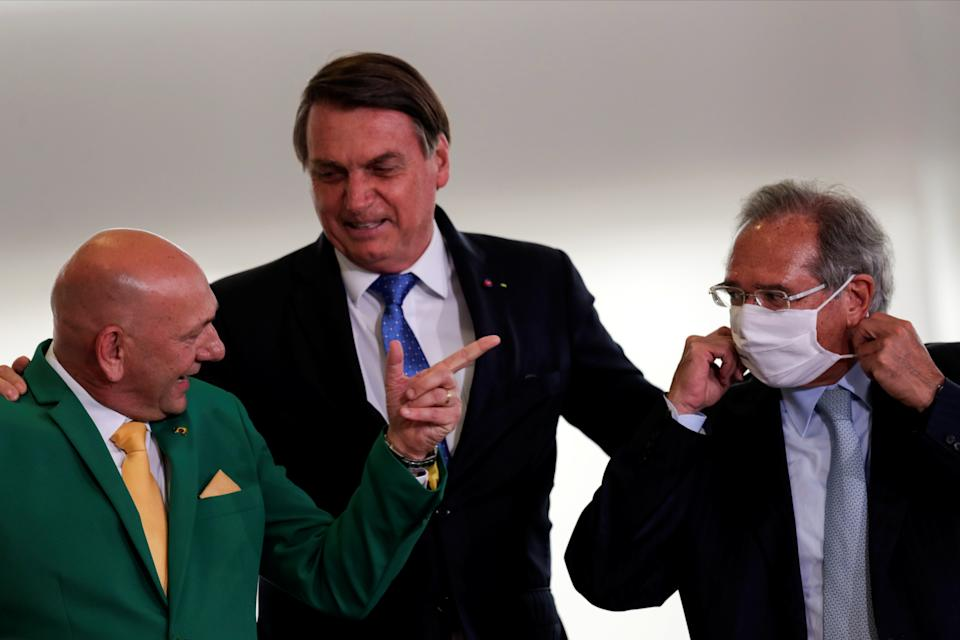 Luciano Hang, co-founder of Grupo Havan, Brazil's President Jair Bolsonaro and Brazil's Economy Minister Paulo Guedes are seen before launching ceremony of the Voo Simples program, which are a set of measures to modernize rules and reduce costs in the general aviation sectors, at the Planalto Palace in Brasilia, Brazil, October 7, 2020. REUTERS/Ueslei Marcelino