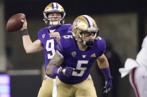 Washington quarterback Dylan Morris, left, drops to pass as running back Sean McGrew (5) takes off from the line of scrimmage during the second half of an NCAA college football game against Utah, Saturday, Nov. 28, 2020, in Seattle. (AP Photo/Ted S. Warren)