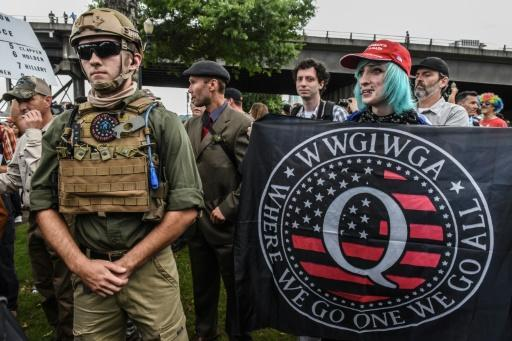 A person holds a banner for the Qanon conspiracy theory movement during an alt-right rally in Portland, Oregon in August 2019