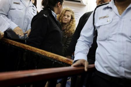 Palestinian teen Ahed Tamimi enters a military courtroom escorted by Israeli security personnel at Ofer Prison, near the West Bank city of Ramallah, February 13, 2018. REUTERS/Ammar Awad