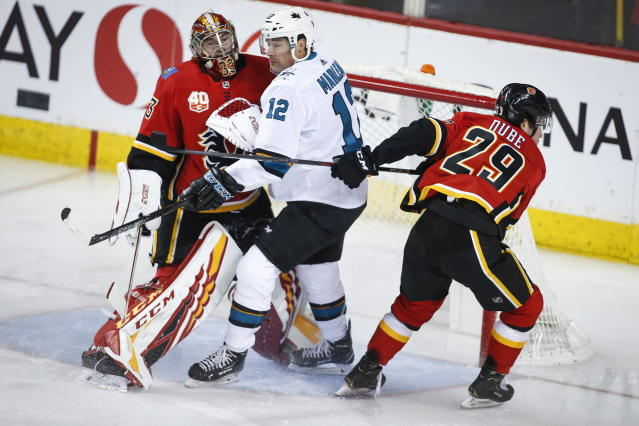 San Jose Sharks' Patrick Marleau, center, is sandwiched between Calgary Flames goalie David Rittich, left, and Dillon Dube during the first period of an NHL hockey game, Tuesday, Feb. 4, 2020 in Calgary, Alberta. (Jeff McIntosh/The Canadian Press via AP)