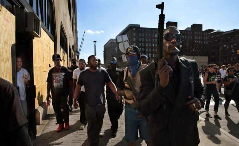Armed protesters march in downtown St. Louis as a man from a boarded up dry cleaners watches through the doorway after former St. Louis police officer Jason Stockley was acquitted in the shooting death of Anthony Lamar Smith on Friday, Sept. 15.