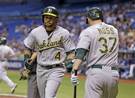 Oakland Athletics center fielder Coco Crisp (4) celebrates with on-deck batter Brandon Moss after scoring on a first-inning single by teammate Jed Lowrie off Tampa Bay Rays starting pitcher Alex Cobb during a baseball game on Friday, April 19, 2013, in St. Petersburg, Fla. (AP Photo/Chris O'Meara)