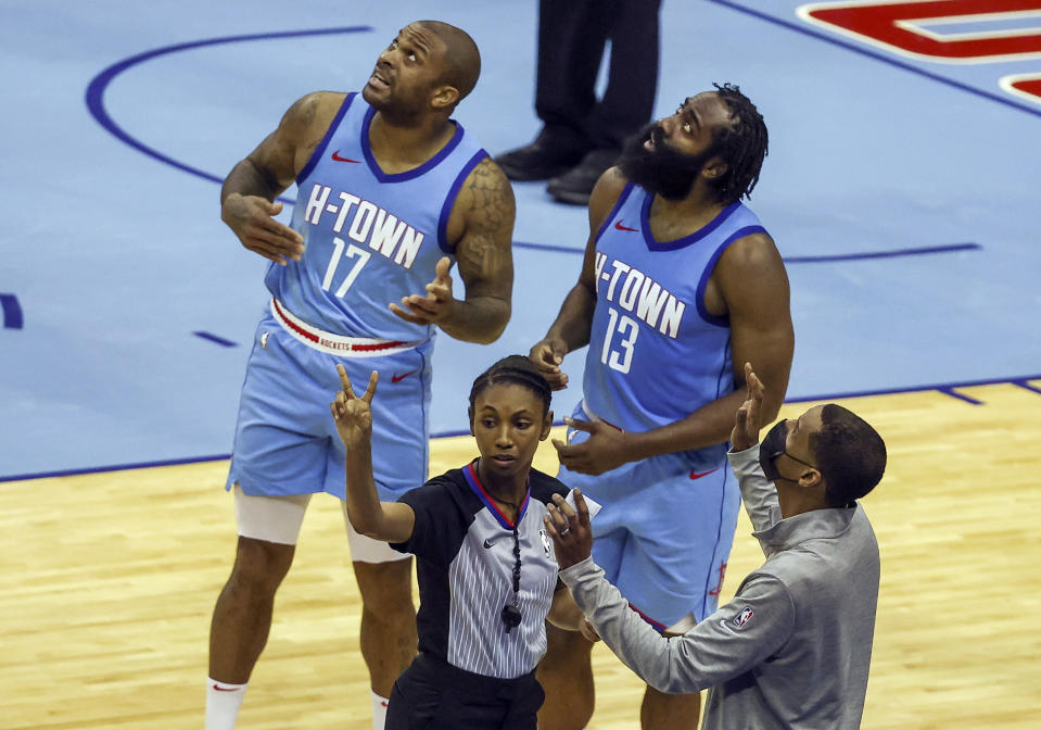 Houston Rockets forward P.J. Tucker (17) and guard James Harden (13) and Rockets coach Stephen Silas, front right, watch a replay after a call during the third quarter against the Los Angeles Lakers in an NBA basketball game Tuesday, Jan. 21, 2021, in Houston. (Troy Taormina/Pool Photo via AP)