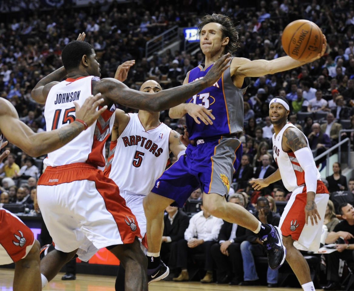 Suns Nash passes the ball off around Raptors Johnson, Bayless, and Johnson during their NBA basketball game in Toronto. 2011. Mark Blinch / Reuters