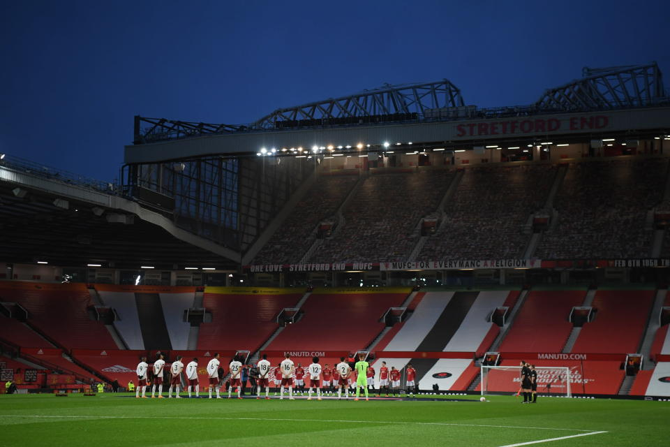 Manchester United and Arsenal players take part in a minute of silence as a soldier at left lays a wreath during the English Premier League soccer match between Manchester United and Arsenal at the Old Trafford stadium in Manchester, England, Sunday, Nov. 1, 2020. (Shaun Botterill/Pool via AP)