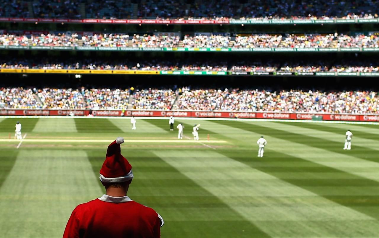 MELBOURNE, AUSTRALIA - DECEMBER 26:  A fan dressed as Santa watches play during day one of the Second Test match between Australia and Sri Lanka at the Melbourne Cricket Ground on December 26, 2012 in Melbourne, Australia.  (Photo by Ryan Pierse/Getty Images)