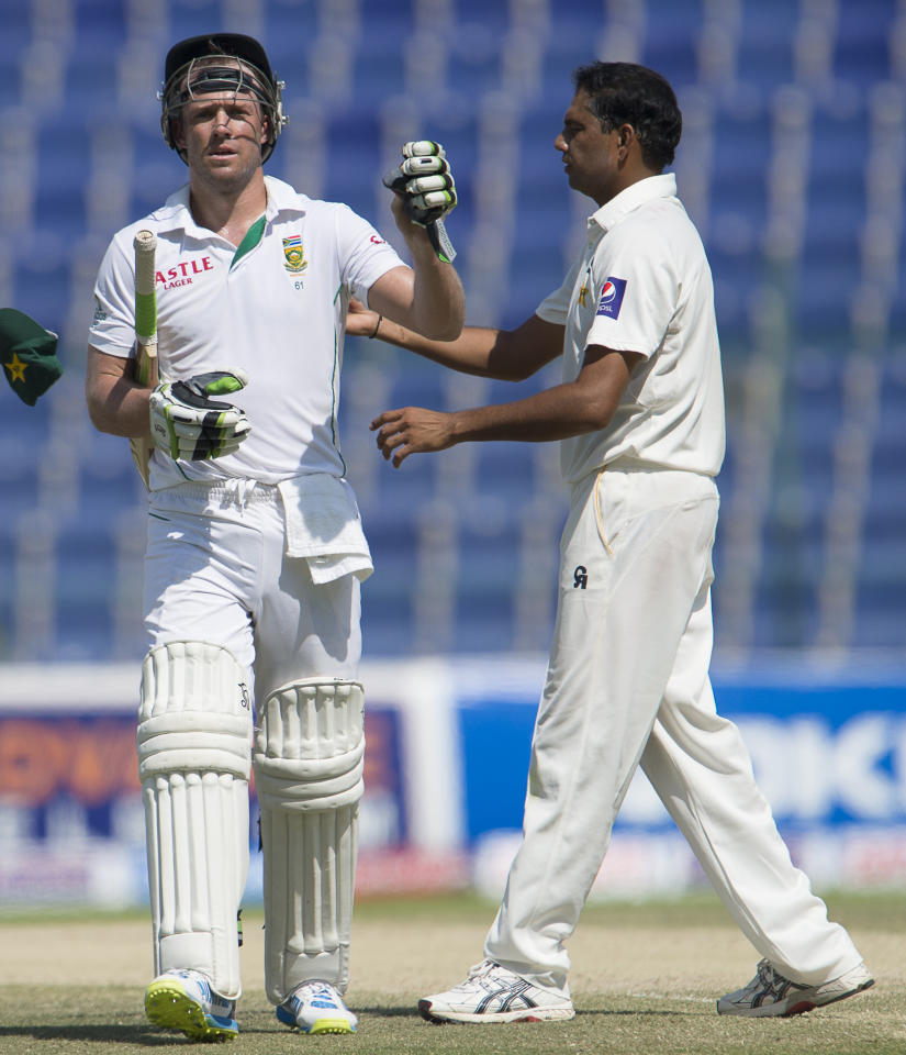South Africa's batsman Ab de Villiers and Pakistan's Zulifqar Babar play on the fourth day of their first Test at the Sheikh Zayed Cricket Stadium in Abu Dhabi on October 17, 2013. AB de Villiers hit a fighting fifty to delay Pakistan's victory march over South Africa on the fourth day of the first Test in Abu Dhabi today. AFP PHOTO/STR          (Photo credit should read STR/AFP/Getty Images)