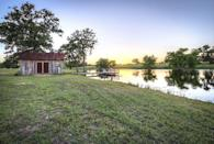 """<p>Talk about a picture perfect country getaway: This custom built 336-square-foot cabin sits on 24 sprawling acres in West Point, Texas—just steps from its own four-acre constant flow lake, tiny lake house, and wooden pier. The rustic wood-paneled interior features a living space, full kitchen, bathroom, and two lofted bedrooms, all housed under a corrugated metal roof. </p><p><a class=""""link rapid-noclick-resp"""" href=""""http://www.estately.com/listings/info/530-justice-rd"""" rel=""""nofollow noopener"""" target=""""_blank"""" data-ylk=""""slk:SEE INSIDE"""">SEE INSIDE</a></p>"""