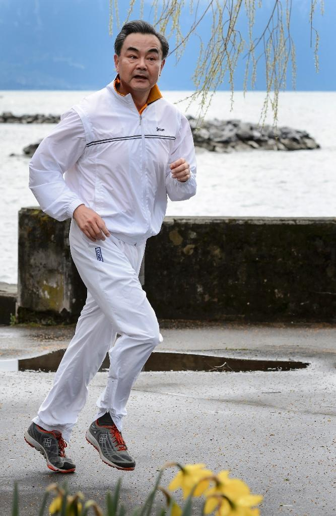 Chinese Foreign Minister Wang Yi jogging along Lake Geneva during on March 30, 2015 (AFP Photo/Fabrice Coffrini)