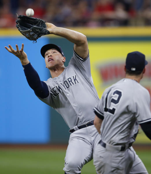 New York Yankees' Aaron Judge, left, makes a catch to get out Cleveland Indians' Rajai Davis for the final out as Tyler Wade (12) gets out of the way during the ninth inning of a baseball game, Saturday, July 14, 2018, in Cleveland. (AP Photo/Ron Schwane)