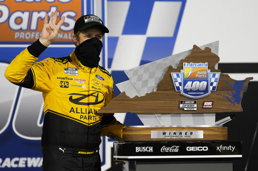 Brad Keselowski poses with the trophy in Victory Lane as he celebrates after winning a NASCAR Cup Series auto race Saturday, Sept. 12, 2020, in Richmond, Va. (AP Photo/Steve Helber)