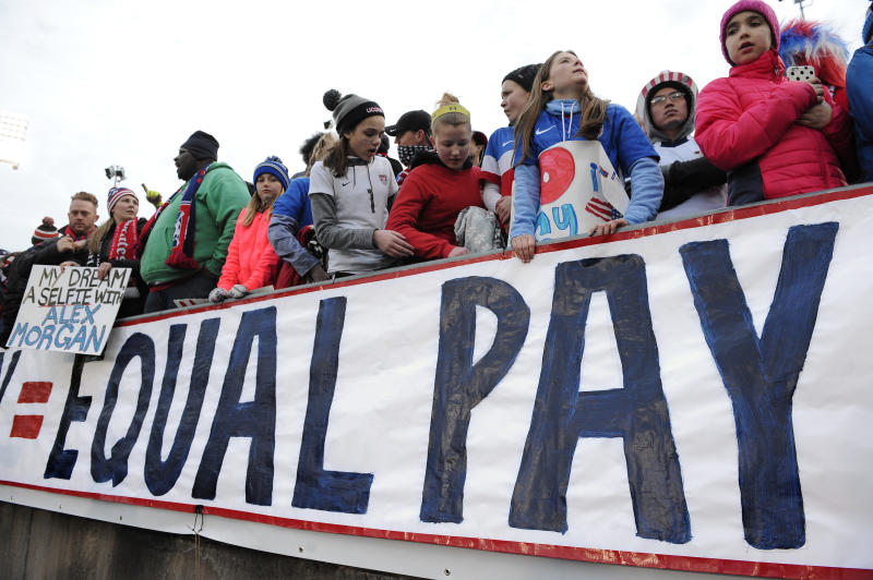FILE - In this April 6, 2016, file photo, fans stand behind a large sign for equal pay for the women's soccer team during an international friendly soccer match between the United States and Colombia at Pratt & Whitney Stadium at Rentschler Field in East Hartford, Conn. The World Economic Forum's annual Global Gender Gap Report released on Oct. 25, 2016, found that the global gender pay gap will not be closed for another 170 years if current trends continue. (AP Photo/Jessica Hill, File)