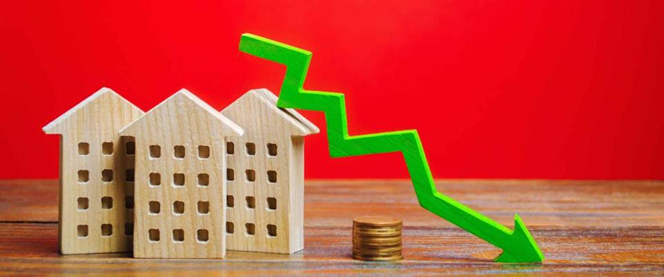 Miniature wooden houses and a green arrow down. The concept of low mortgage rates.