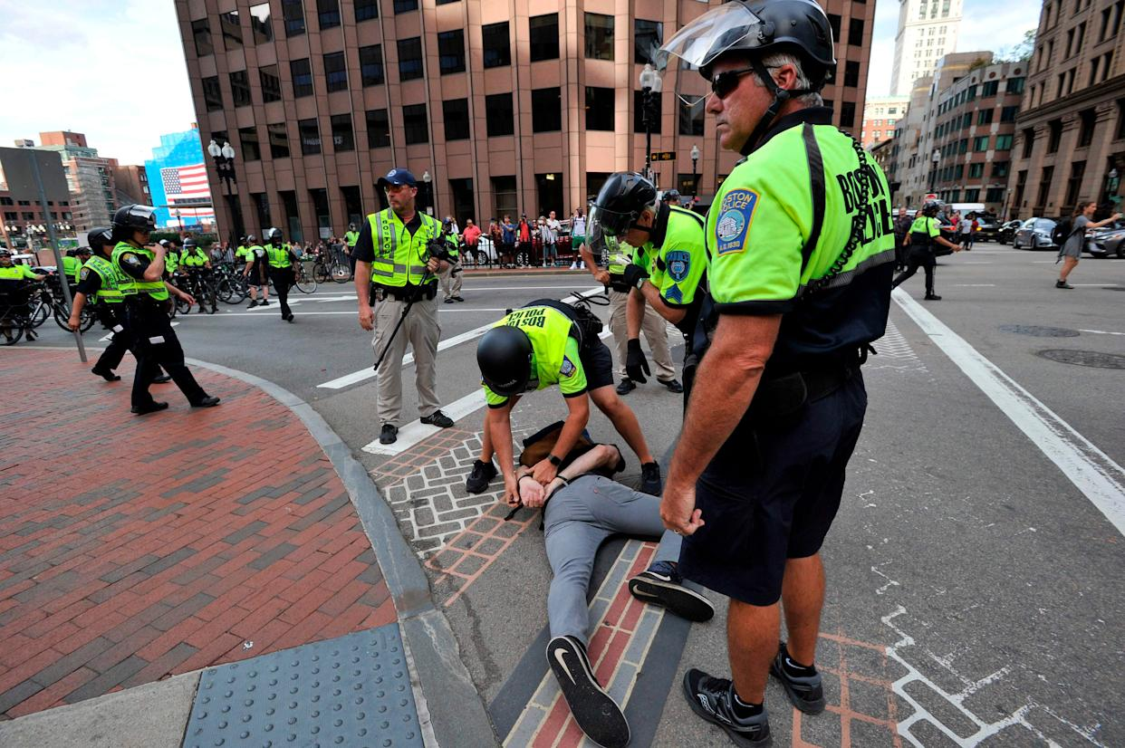 Boston Police officers arrest an anti-parade demonstrator during the