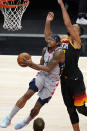 Washington Wizards guard Bradley Beal, left, goes to the basket as Utah Jazz center Rudy Gobert, right, defends in the first half during an NBA basketball game Monday, April 12, 2021, in Salt Lake City. (AP Photo/Rick Bowmer)
