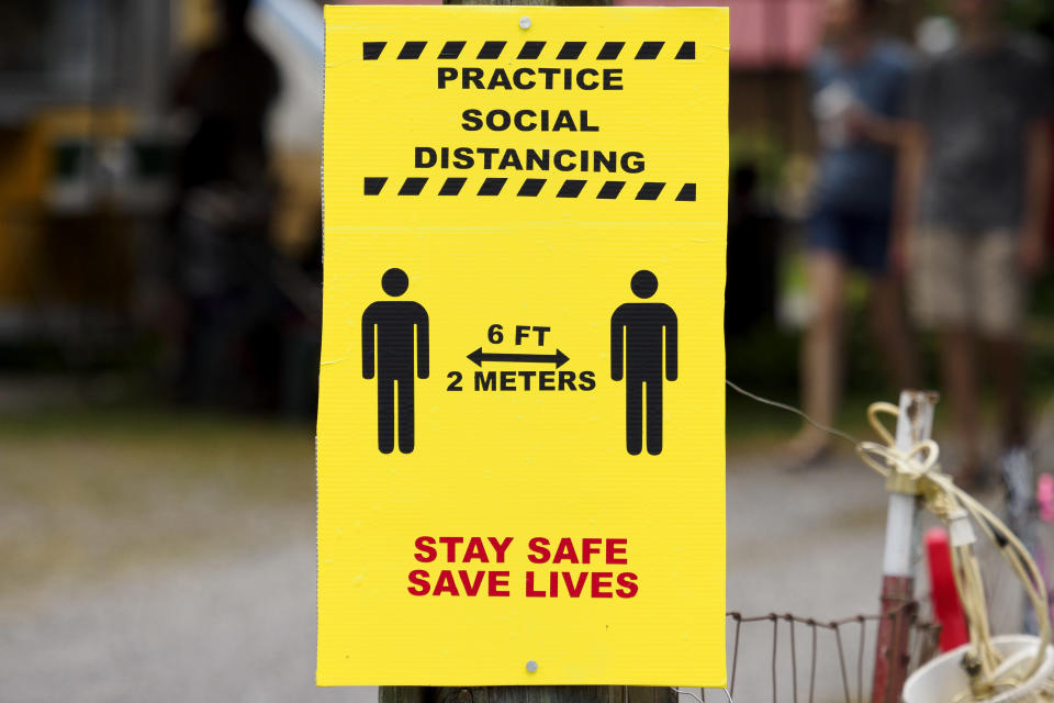 """A sign encouraging social distancing is seen during the """"World's Longest Yard Sale,"""" Sunday, Aug. 9, 2020, in Dunlap, Tenn. The six-state yard sale, which was held despite concerns over the coronavirus pandemic, started Thursday and ended Sunday, and stretched from Alabama to Michigan. (C.B. Schmelter/Chattanooga Times Free Press via AP)"""