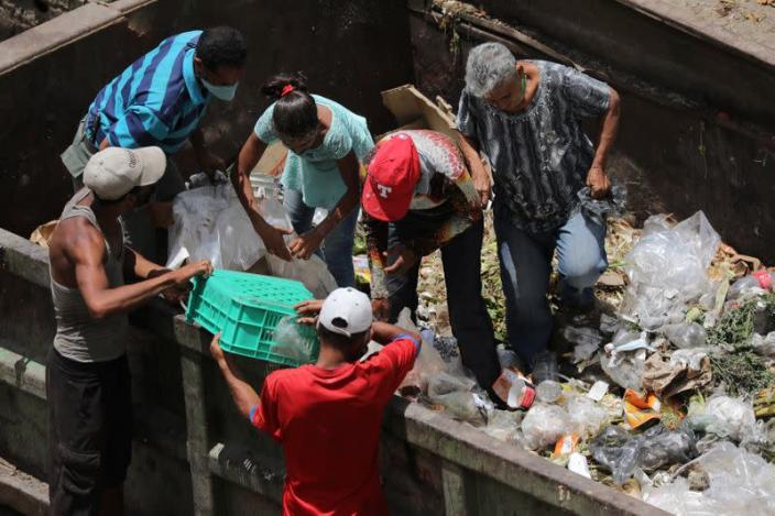People search for food at a garbage container during the closing hour at the Coche wholesale market amid coronavirus (COVID-19) disease outbreak in Caracas