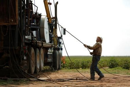 Oil field worker, Miguel Holguin, operates a swabbing rig in a field in Seminole